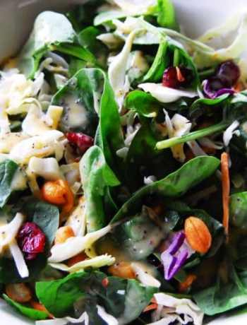 Top view of tossed spinach salad with peach dressing.