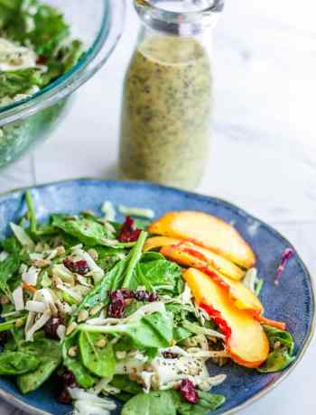 Creamy poppy seed dressing behind a plate of quick spinach salad.