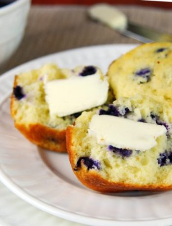 Halved blueberry muffin on a plate next to a whole blueberry muffin, side view.