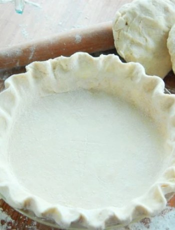 Fluted pie dough in a pie plate next to three portions of pie dough.