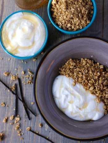 Bowl of yogurt and granola next to two small bowls of yogurt and granola.