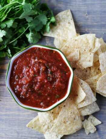 Top view of restaurant style salsa next to some chips and cilantro.
