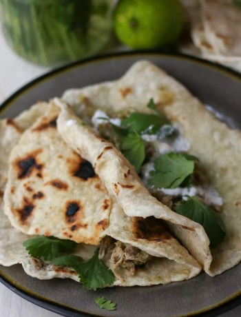 Pork street tacos on a grey plate topped with cilantro.
