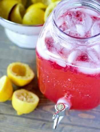 Vat of raspberry lemonade next to spent lemon halves.
