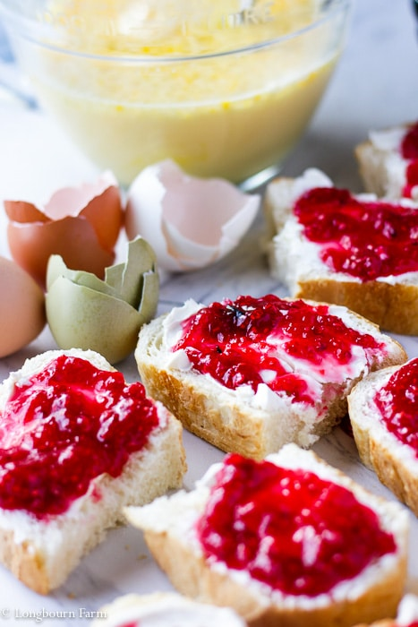 Slices of bread spread with jam and cream cheese, ready to be assembled into overnight french toast bake.
