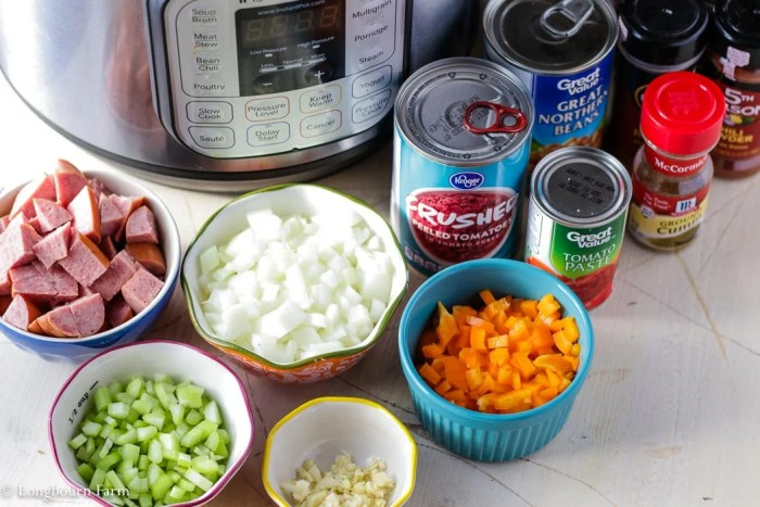 Ingredients for Instant Pot chili: diced onion, diced pepper, diced celery, minced garlic, chopped sausage, and cans of tomato sauce, tomato past, and beans next to an Instant Pot 8 quart.