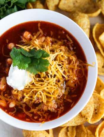 Instant pot chili in a bowl topped with shredded cheese, sour cream, and cilantro next to a bunch of cilantro and some corn chips.