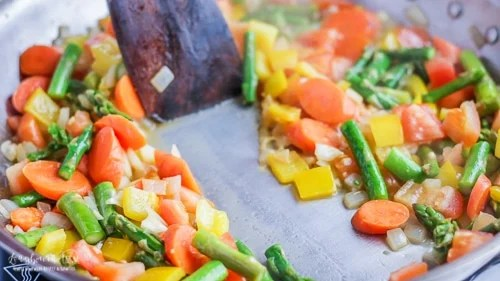 Dragging a wooden spoon through the reduced white wine in the veggies for pasta primavera recipe.