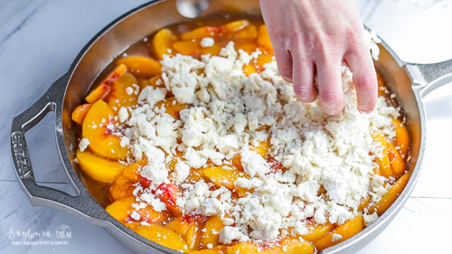 Spreading crumb topping on top of peaches for easy peach cobbler.