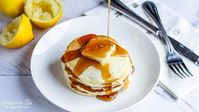 Pouring syrup over lemon ricotta pancakes.