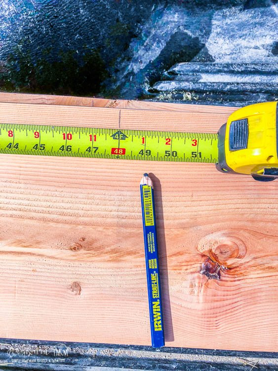 Measuring 4 feet on an 8 foot piece of wood for building raised planter beds.