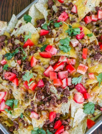 Top view of a finished tray of ground beef nachos topped with cilantro and tomatoes.