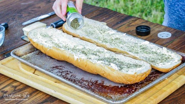 Sprinkling Italian seasoning on buttered french bread for cheesy garlic bread.