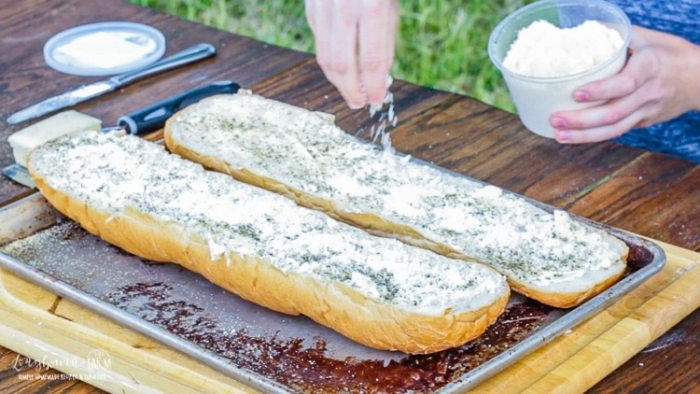 Sprinkling cheese on halves of buttered french bread for cheesy garlic bread.