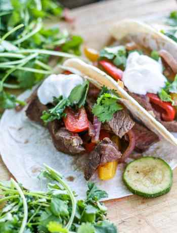 Close-up of steak fajita recipe on flour tortillas.