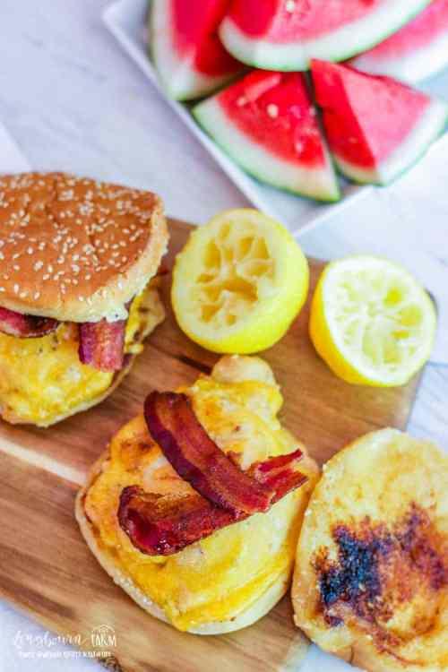 Open chicken bacon sandwich on a cutting board.