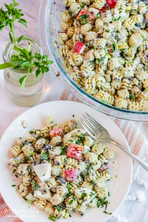 Plate of easy macaroni salad recipe next to a bowl of it.
