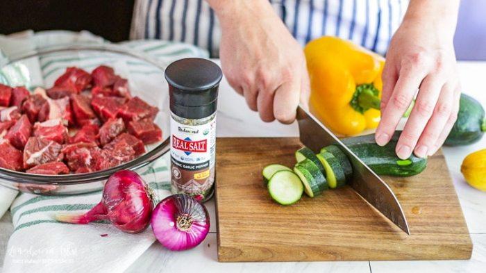Chopping green zucchini for steak kabobs.