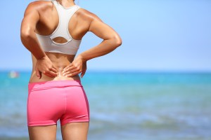 Back pain. Athletic woman in pink sportswear standing at the seaside rubbing the muscles of her lower back, cropped torso portrait.