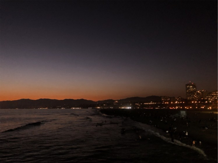 The sun is just below the horizon of the Santa Monica pier. The sky is orange near the horizon and deep blue at the top of the photo. The fading light reflects on the ocean in front of a city-lit pier.