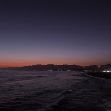 Deep blue sky, oragne sunset around mountains, lights sprinkled on santa monica pier, ocean reflecting sunset in the foreground
