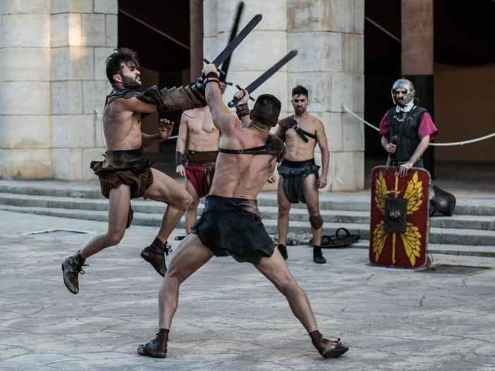shirtless men fighting with sword