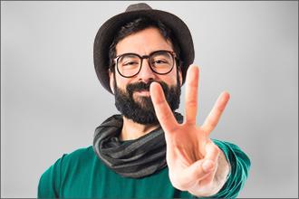 Mann mit Brille zeigt drei Finger und grinst dabei