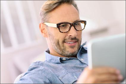 Mann mit Muster-Brille sitzt auf der Couch