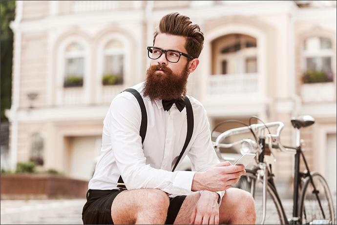Stylischer Mann kombiniert Brille mit Fliege und Hosenträgern