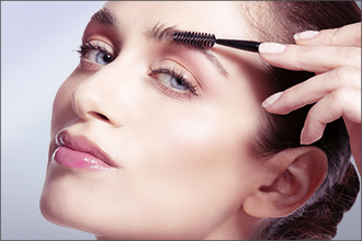 Frau schminkt sich die Augenbrauen mit einer Augenbrauenbürste