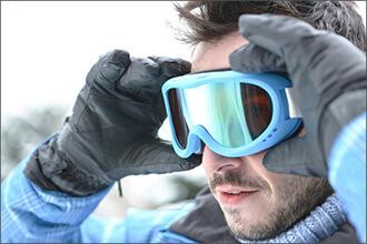 Mann setzt Skibrille mit getönten Gläsern auf