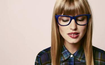 Frau mit Brille beißt sich auf die Lippe
