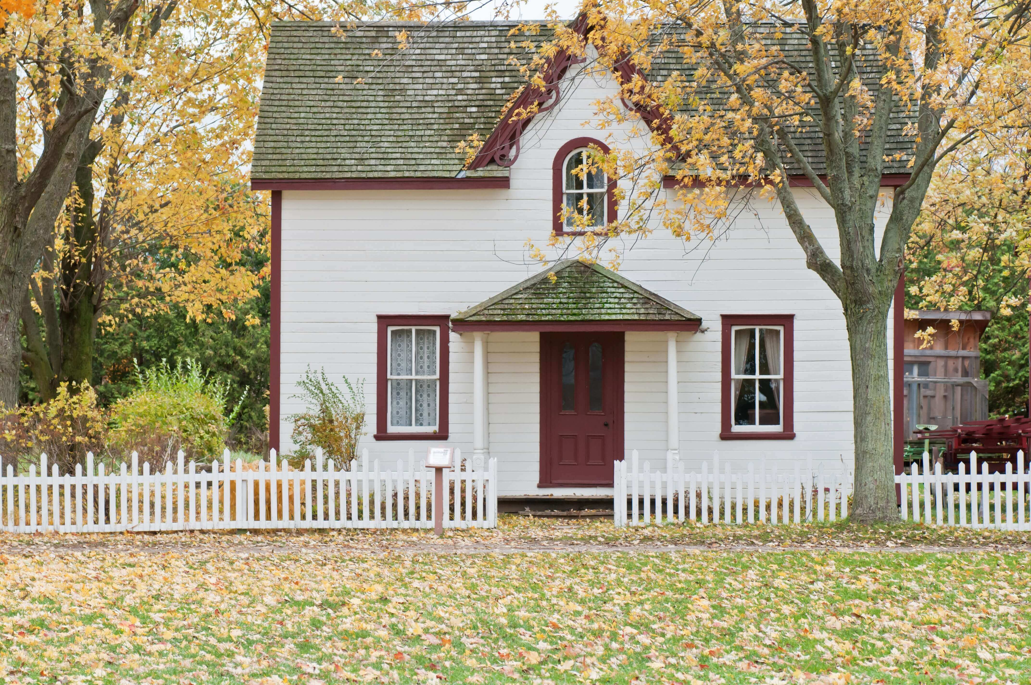 Image shows a white house in a leafy area. Represents the simple lifestyle attached to frugal living.