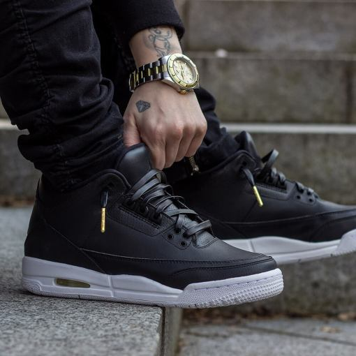 black jordans with black leather shoelaces with gold tips