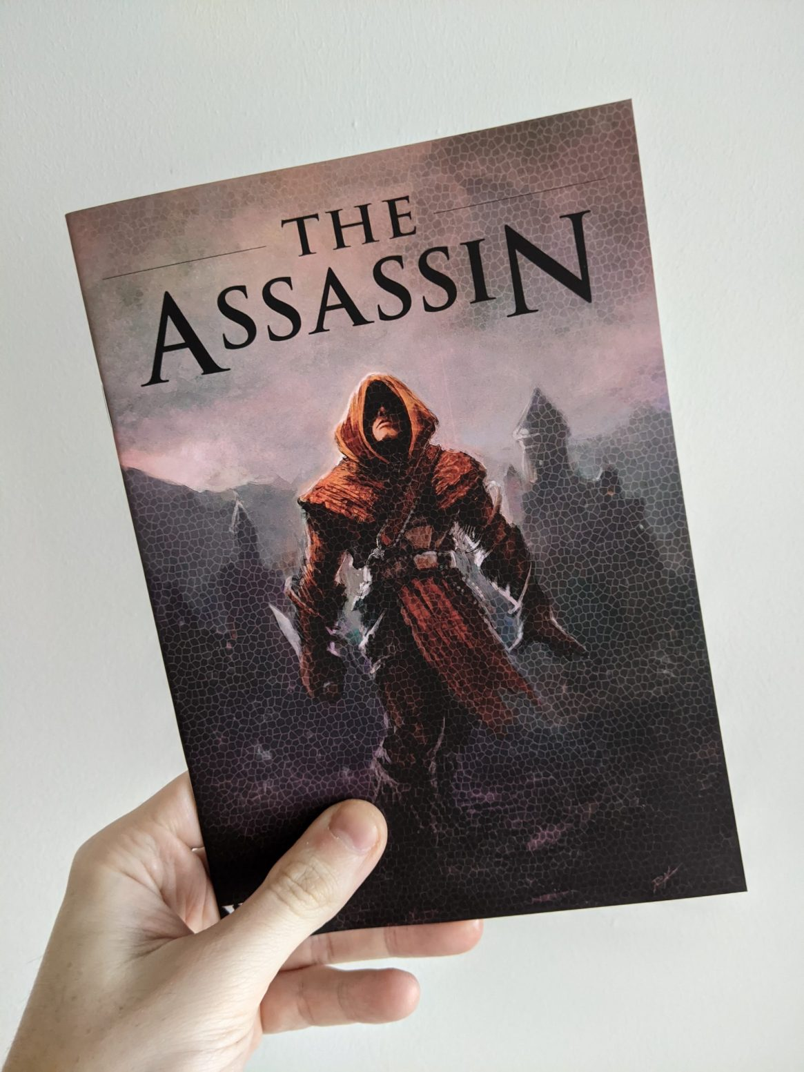 """A hand holding a print zine against a white wall.. The cover shows a hooded figure in red robes holding a large knife, walking away from a city skyline. The title reads """"The Assassin""""."""