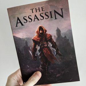"A hand holding a print zine against a white wall.. The cover shows a hooded figure in red robes holding a large knife, walking away from a city skyline. The title reads ""The Assassin""."