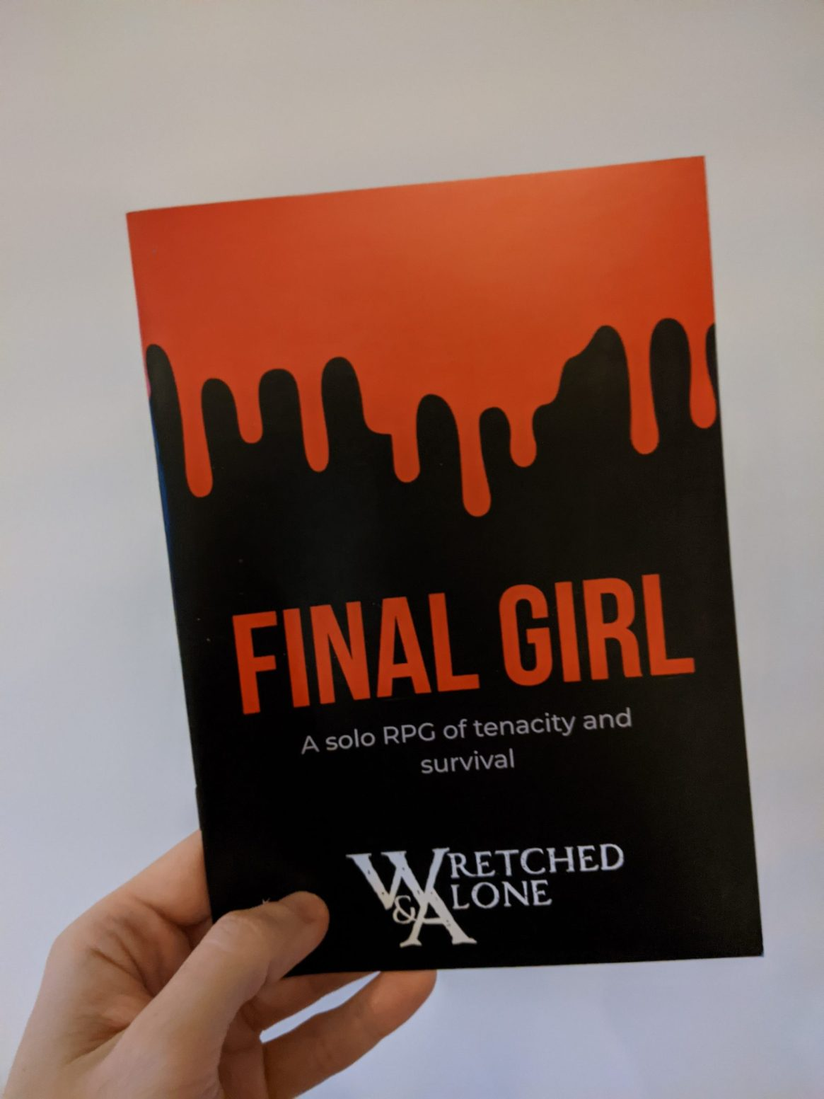 A hand holding an A5 print zine. Blood drips down the black cover towards the words FINAL GIRL in bold all-caps. The Wretched & Alone logo is visible at the bottom of the page.