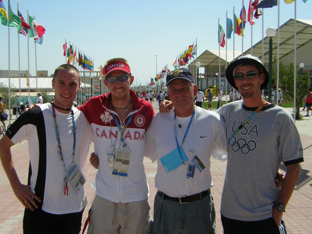 Ron Warhurst, with 2004 Olympians (from L to R) Nick Willis, Kevin Sullivan, and Tim Broe. (Courtesy Michigan Athletics)