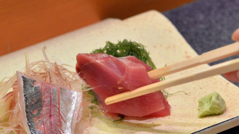 This photo taken on July 16, 2013 shows a customer eating bonito and horse mackerel sashimi (raw fish) at a high-end sushi restaurant in Tokyo.  There is no menu and the chef selects the best fish available for customers, which costs at least 10,000 yen (100 USD) per person. While high-end restaurants cater to regular clientËle, many traditional sushi restaurants - a business steeped in tradition - nowadays must compete with