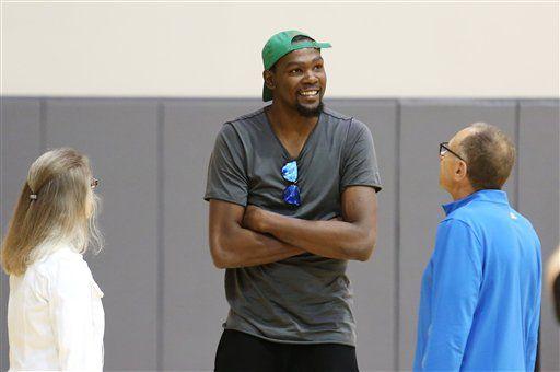 Kevin Durant no asistiría a la Casa Blanca - Kevin Durant, centro, conversa con el asistente de los Warriors, Ron Adams, derecha, antes de una conferencia de prensa para presentarlo como nuevo jugador de Golden State el jueves, 7 de julio de 2016, en Oakland, California. (AP Photo/Beck Diefenbach)
