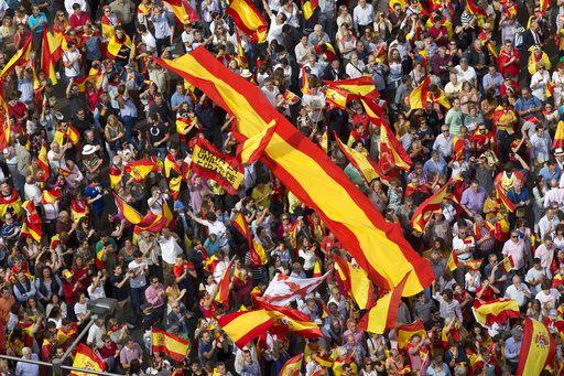 Tribunal Constitucional de España suspende sesión del Parlamento catalán - En esta fotografía del sábado 30 de septiembre de 2017 se muestra a gente sosteniendo banderas en la Plaza de la Cibeles en Madrid, España. Miles de simpatizantes de la unidad española se reunieron para manifestarse en contra del referendo catalán sobre la independencia de la región de España. (AP Foto/Paul White)