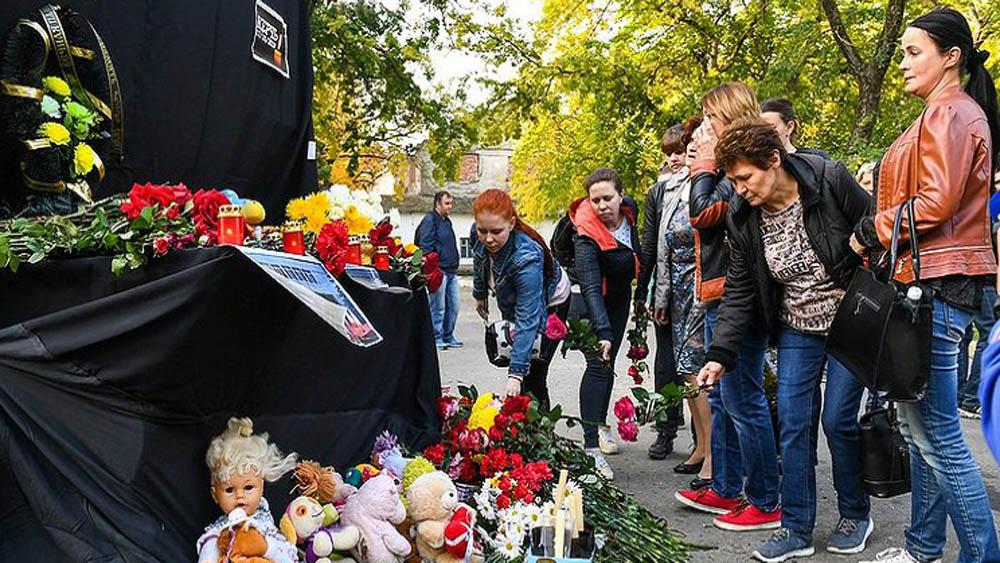 Recuerdan con flores, veladoras y peluches a víctimas de matanza en secundaria de Kerch, Crimea. Foto de Internet