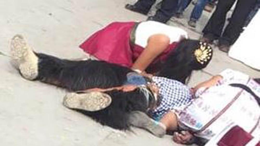 Mujeres junto al cuerpo del danzante asesinado en Oaxaca. Foto de Internet