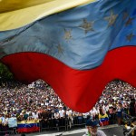 Jornada de protestas en Venezuela - A Venezuelan national flag flutters during a mass opposition rally against President Nicolas Maduro in which Venezuela's National Assembly head Juan Guaido (out of frame) declared himself the country's