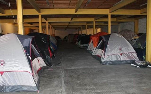 Migrantes se rehúsan a dejar albergue clausurado en Tijuana - Casas de campaña de migrantes dentro de bodega. Foto de @RadioProgresoHN