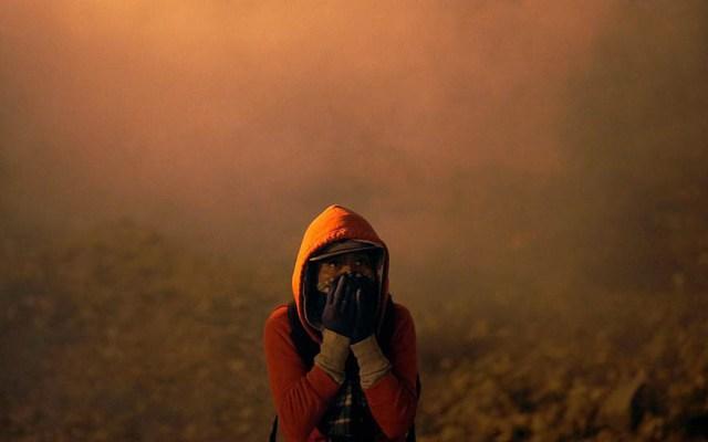 Frenan con gas lacrimógeno cruce de ilegales a San Diego desde Tijuana - Migrante cubriéndose del gas lacrimógeno. Foto de Reuters