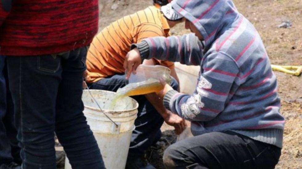 No se dará marcha atrás en combate a robo de combustible: Pemex - Personas recolectando combustible. Foto de AFP