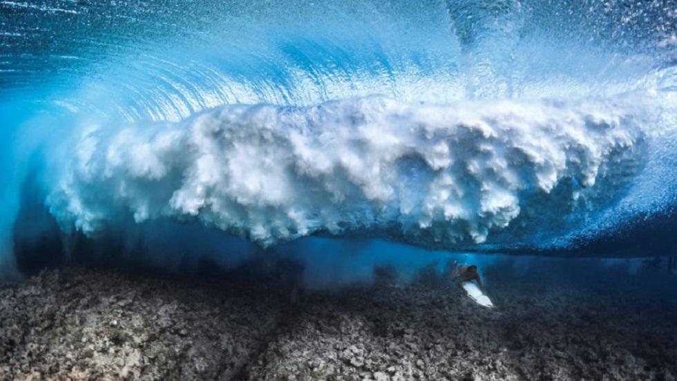 Surfista nadando debajo de una ola en la isla de Rangiroa, en la Polinesia Francesa. Foto de Greg Lecoeur