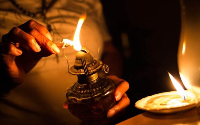 Venezuela alarga suspensión de clases y jornada laboral por apagón - Cientos de venezolanos pasan las noches con velas encendidas ante el apagón masivo que los afecta desde hace tres días. Foto de AFP / Cristian Hernández