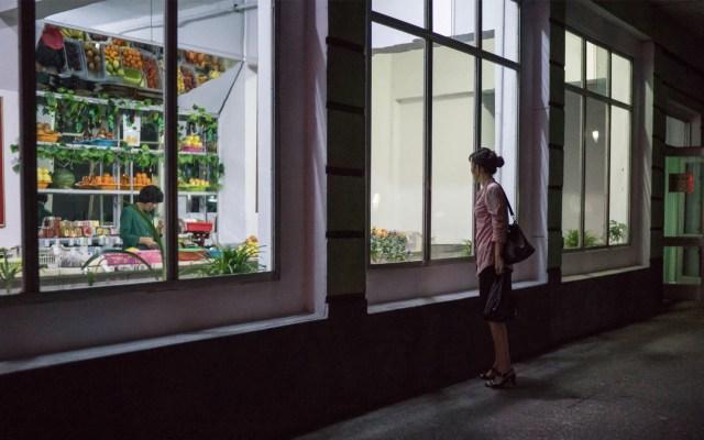 Corea del Norte registra su peor cosecha en 10 años - Foto de archivo tomada el 26 de septiembre de 2017. Una mujer de pie frente a una tienda de comestibles en una calle de Pyongyang, Corea del Norte. Foto de Ed Jones/AFP